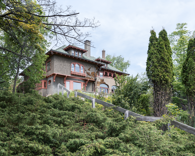 A craftsman style house sitting on a bluff encased in foiliage with a wallpaper detail on the exterior of the house