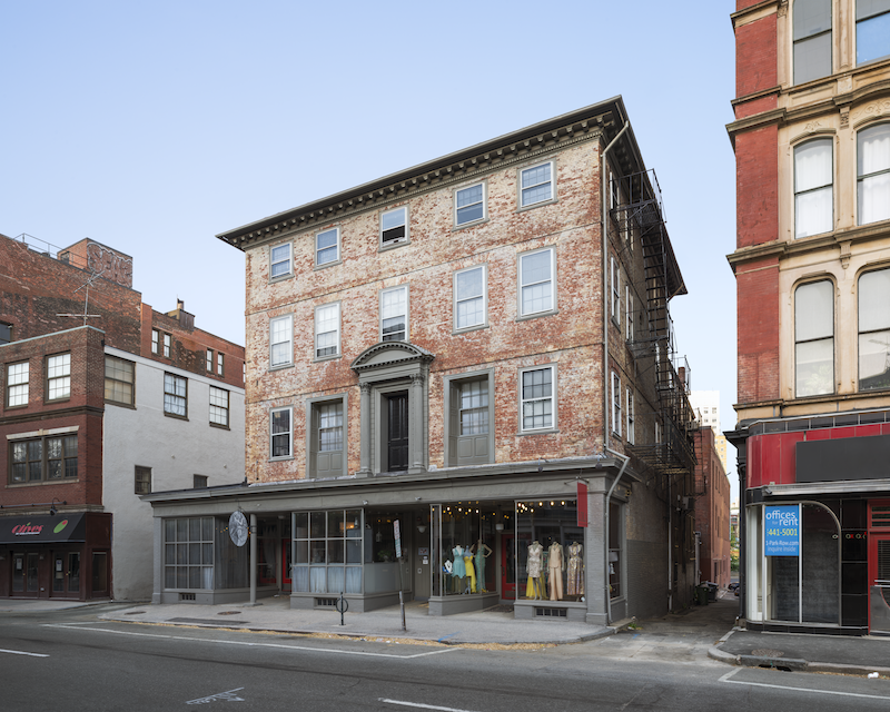 A weathered brick building with a storefront in the street level. the interior woodworking is on the exterior of the second level