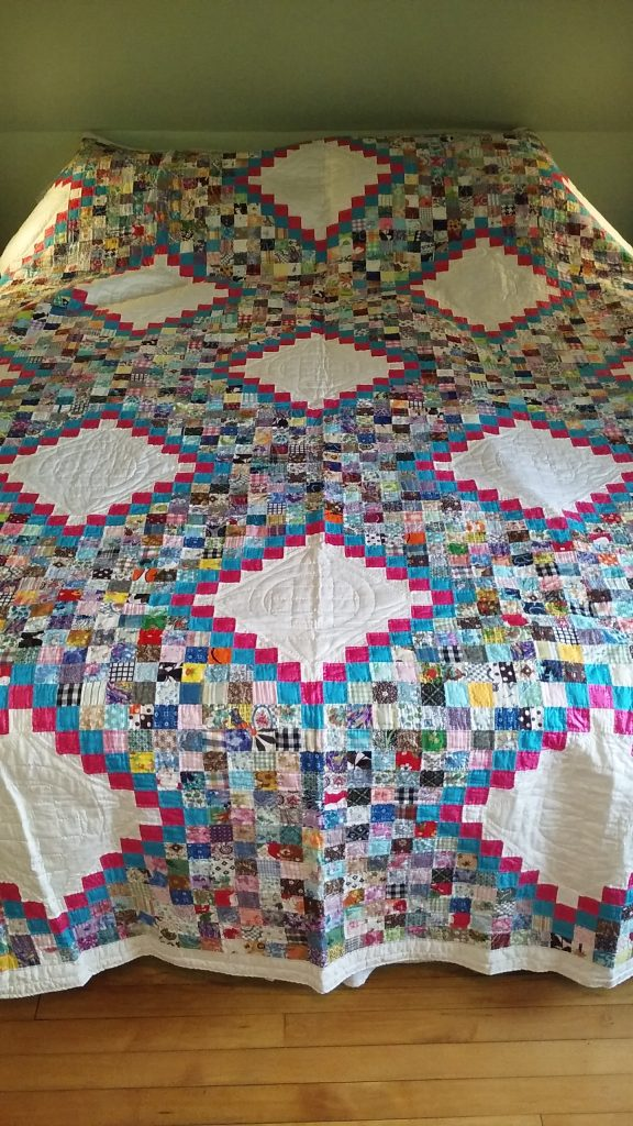 """The quilt in the """"Rainbow Round the World"""" pattern made and given to me by my grandmother."""
