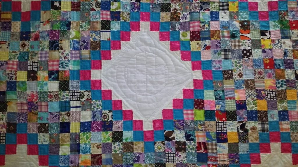 A detail of the quilt, with its myriad one-inch squares.